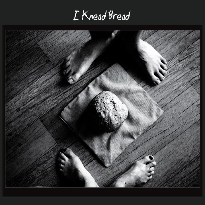 a loaf of bread on the floor, two pairs of feet on either sides of it