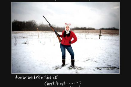 Girl standing in snowy field, smiling while holding shotgun pointed at sky