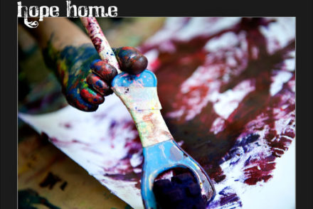 paint-covered foot holding paintbrush, painting