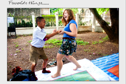A girl and a young boy dance in a front yard