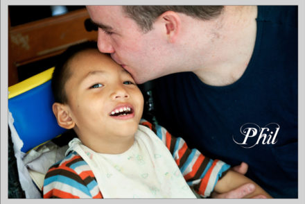 young man kissing a small child on the forehead