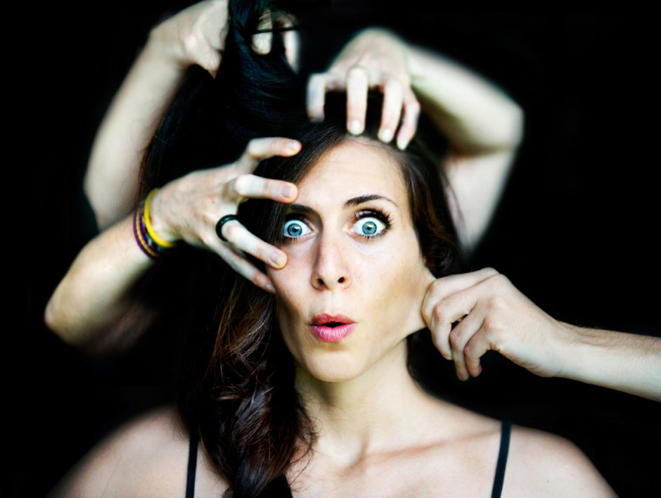 Girl with surprised expression faces camera, numerous hands are pulling at her face and hair