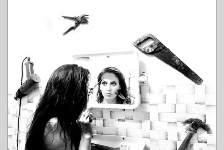 Girl looking in mirror, applying makeup